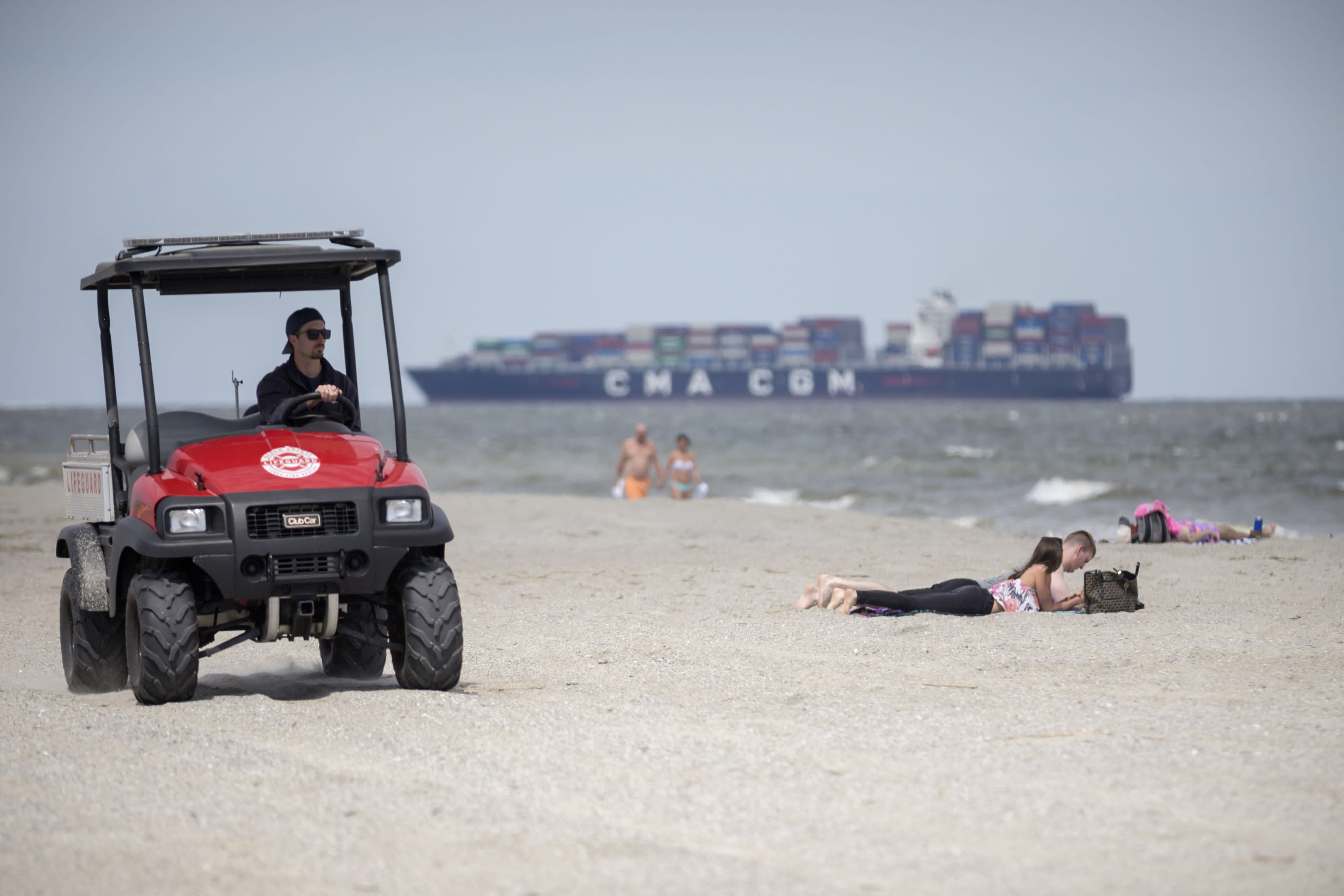 A member of the Tybee Island, Ga., Life Guards, left, patrols the beach on an ATV while visitors sunbathe on the sand after Gov. Bryan Kemp signed an executive order allowing people to exercise outside, with social distancing of at least six feet because of the coronavirus outbreak. (Stephen B. Morton/Atlanta Journal-Constitution via AP)