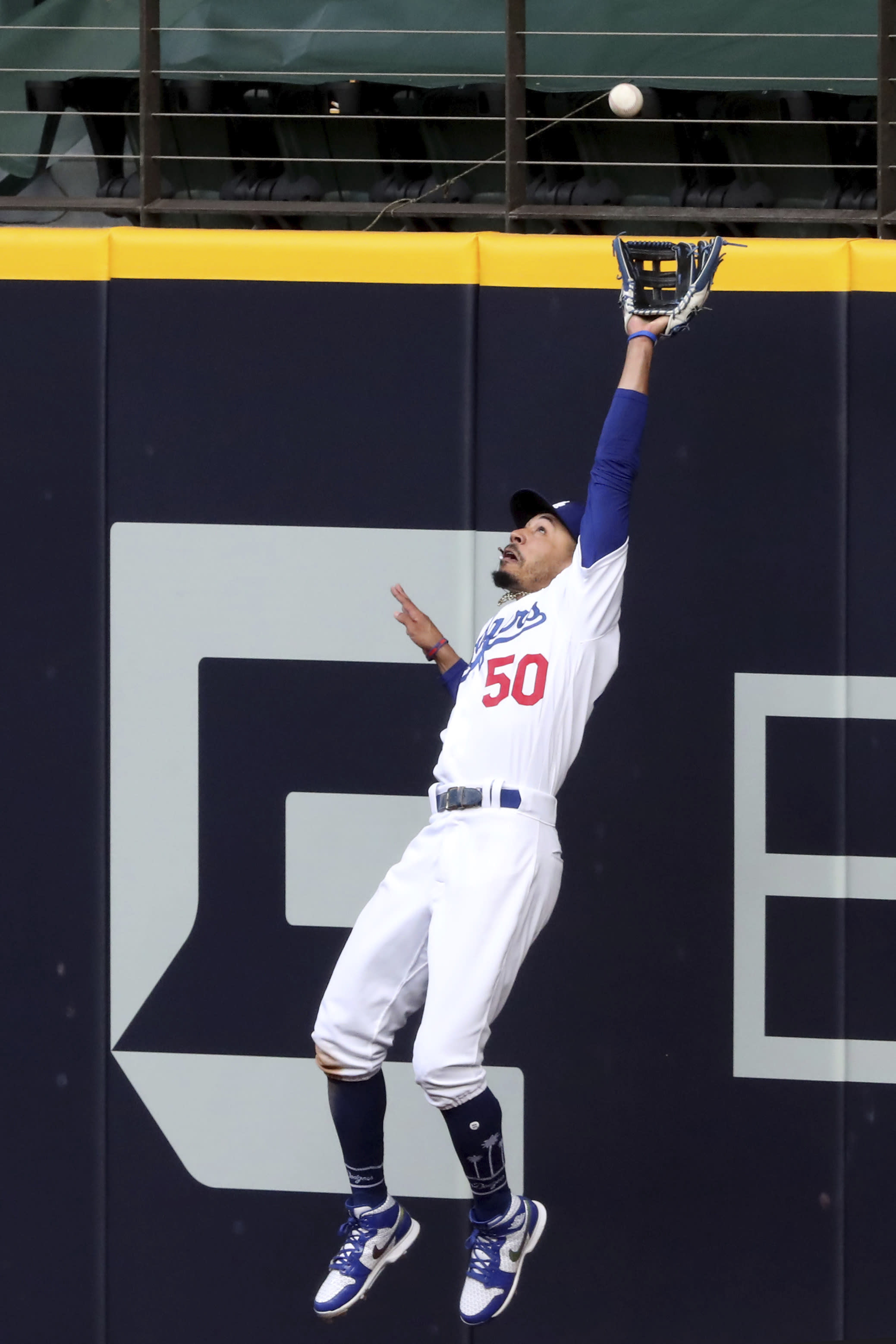 Los Angeles Dodgers right fielder Mookie Betts makes a catch against the outfield wall robbing a home run from Atlanta Braves designated hitter Marcell Ozuna of a hit during the fifth inning in Game 6 of baseball's National League Championship Series, Saturday, Oct. 17, 2020, in Arlington, Texas. (Curtis Compton/Atlanta Journal-Constitution via AP)