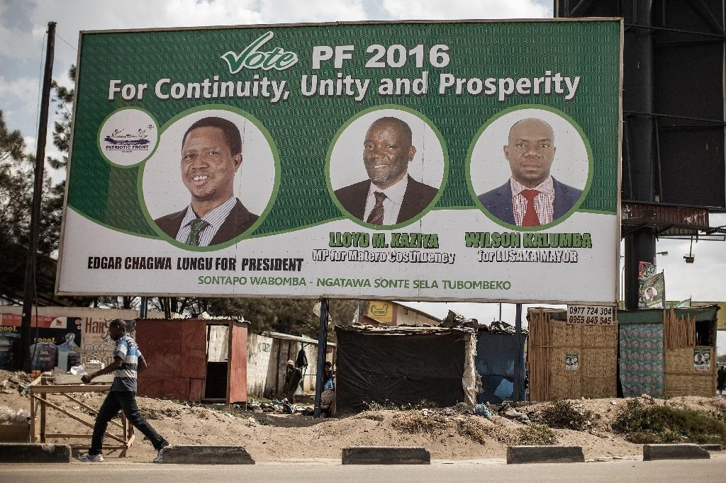People walk by a billboard with picture of the incumbent president Edgar Lungu, of the Patriotic Front ruling Party, two days ahead of Zambian Presidential and legislative elections on August 9, 2016 (AFP Photo/Gianluigi Guercia)