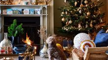 This house is elegantly decorated for Christmas with traditional greenery and lustrous gold and silver