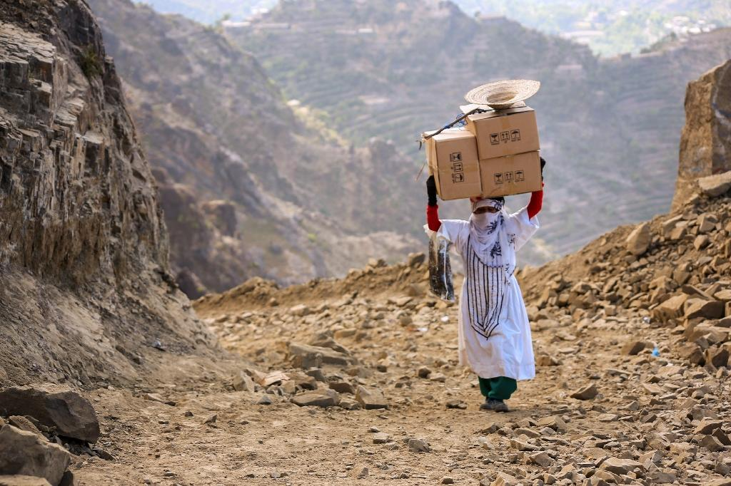 A Yemeni woman carries boxes of food on her head as she walks through the mountains along the only path accessible between the southern cities of Aden and Taez on December 26, 2015 (AFP Photo/Ahmad Al-Basha)