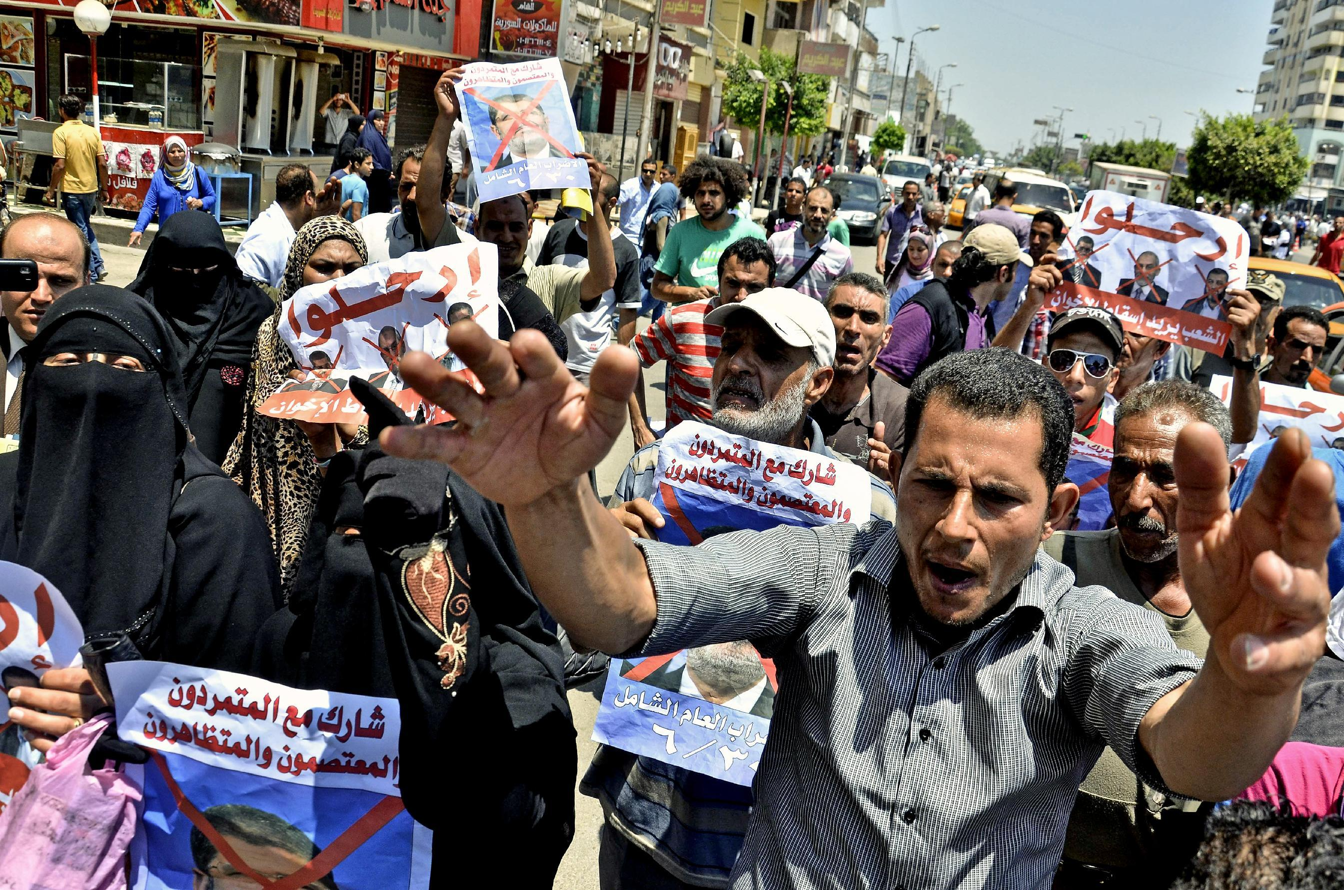 """Protesters chant slogans against Egyptian President Mohammed Morsi outside a court in Ismailia, 139 Kilometers (86 miles) from Cairo, Egypt, Sunday, June 23, 2013. An Egyptian court on Sunday said Muslim Brotherhood members conspired with Hamas, Hezbollah and local militants to storm a prison in 2011 and free 34 Brotherhood leaders, including Morsi. The poster, bottom left, in Arabic reads, """"join the rebels, the protesters, and demonstrators.""""(AP Photo/Mostafa Darwish)"""