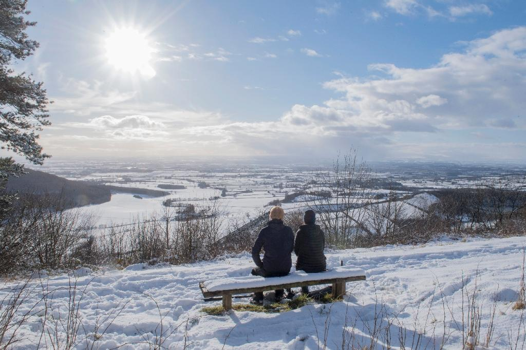 A couple sit on a bench overlooking the snow-covered fields of Thirsk in the North Yorks Moors National Park in North Yorkshire, on February 27, 2018 (AFP Photo/Anthony Devlin)