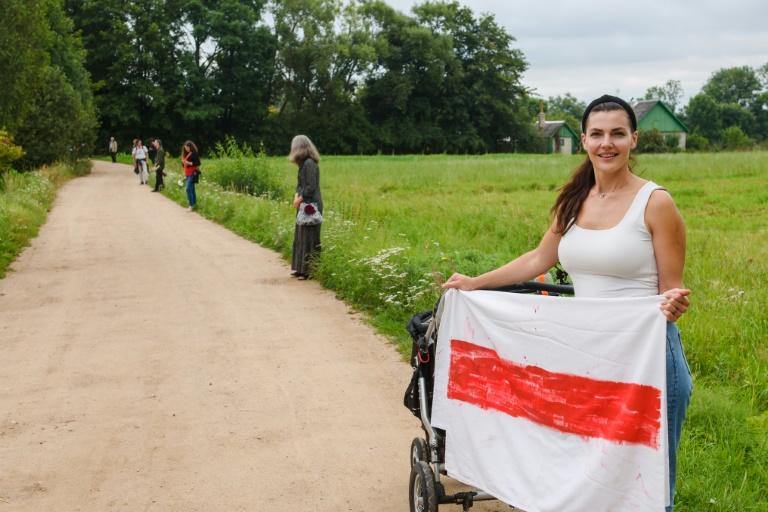 A woman holds a Belarussian opposition flag during a solidarity campaign for Belarussians along the border with Belarus in Piedruja, Latvia.