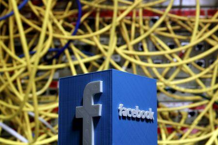 A 3D plastic representation of the Facebook logo is seen in front of displayed cables in this illustration in Zenica