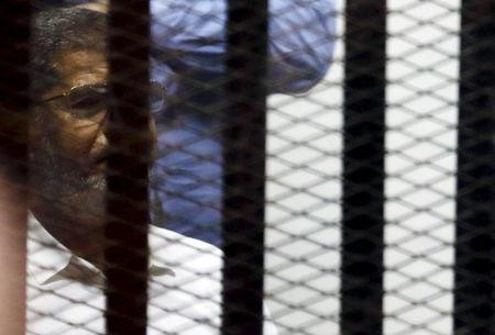 Ousted Egyptian President Mohamed Mursi looks on from behind bars, along with other Muslim Brotherhood members at a court in the outskirts of Cairo
