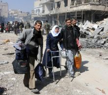 Thousands of Syrians flee raging assaults on two fronts