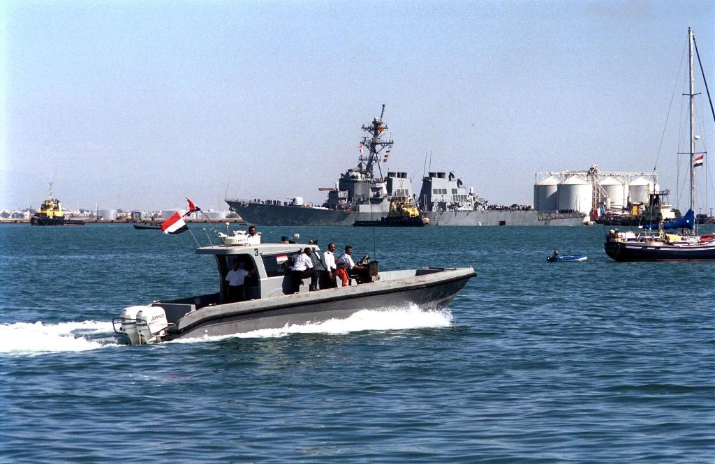 Yemeni marine police patrol around the damaged destroyer USS Cole as it is towed out of Aden harbor on October 29, 2000 -- US President Donald Trump has confirmed that a key plotter of the attack was killed in a US air strike