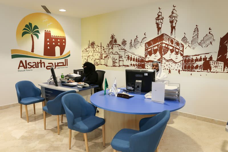 Employees sit behind their desks, as they wait for customers at a travel agency in Riyadh
