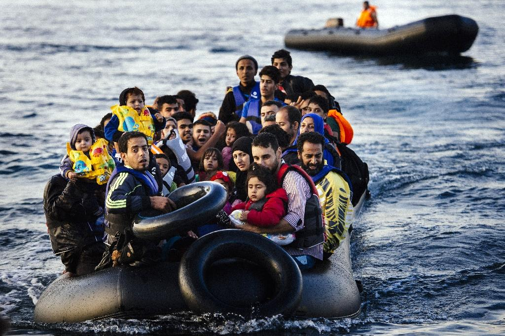 Migrants and refugees arrive on a dinghy on the Greek island of Lesbos on October 14, 2015