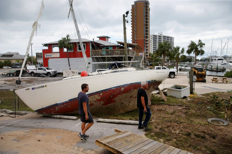 People walk past a boat washed ashore after Hurricane Sally in Pensacola Beach
