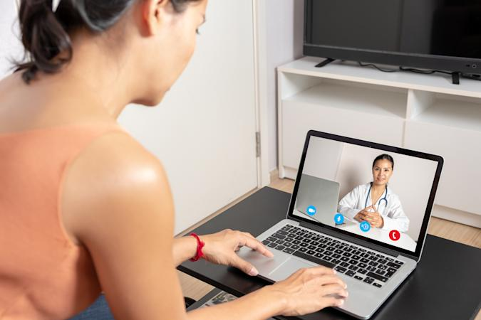 Woman using a laptop for a video call webcam with a doctor