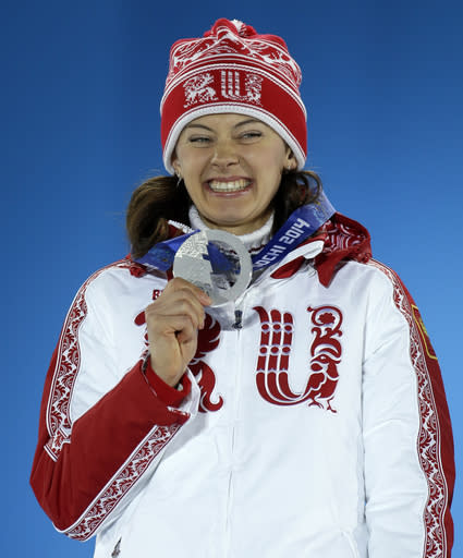 FILE - In this Monday, Feb. 10, 2014 file photo, women's 7.5K sprint silver medalist Olga Vilukhina of Russia smiles with her medal during the medals ceremony at the 2014 Winter Olympics, in Sochi, Russia. Two-time Olympic biathlon champion Olga Zaitseva lost her appeal Thursday Sept. 24, 2020, against disqualification from the 2014 Sochi Olympics for her part in Russias state-backed doping program and two of Zaitsevas relay teammates at Sochi, Olga Vilukhina and Yana Romanova, won their appeals and had their IOC disqualifications from individual biathlon events at Sochi overturned. (AP Photo/Morry Gash, File)