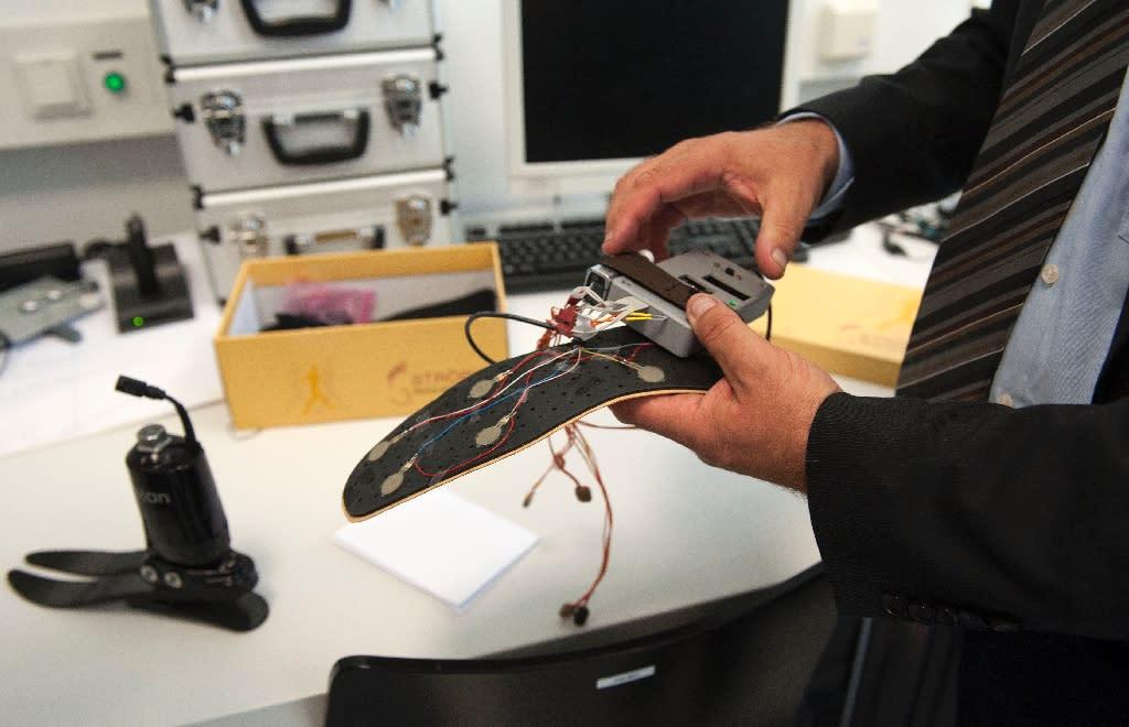 Professor Hubert Egger of Linz University shows a prototype of his 'feeling' leg prosthesis' on June 8, 2015 in Linz (AFP Photo/Samuel Kubani)