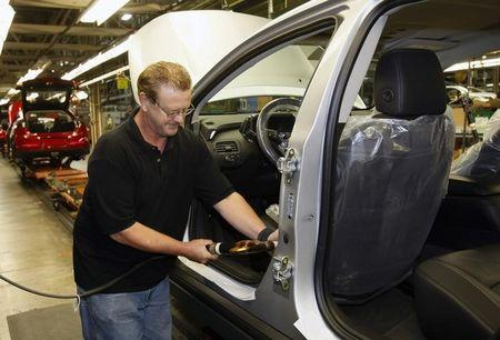 United Auto Workers union member Gary Phillips secures a seat belt in a Chevrolet Volt electric vehicle at General Motors Detroit-Hamtramck assembly plant in Hamtramck