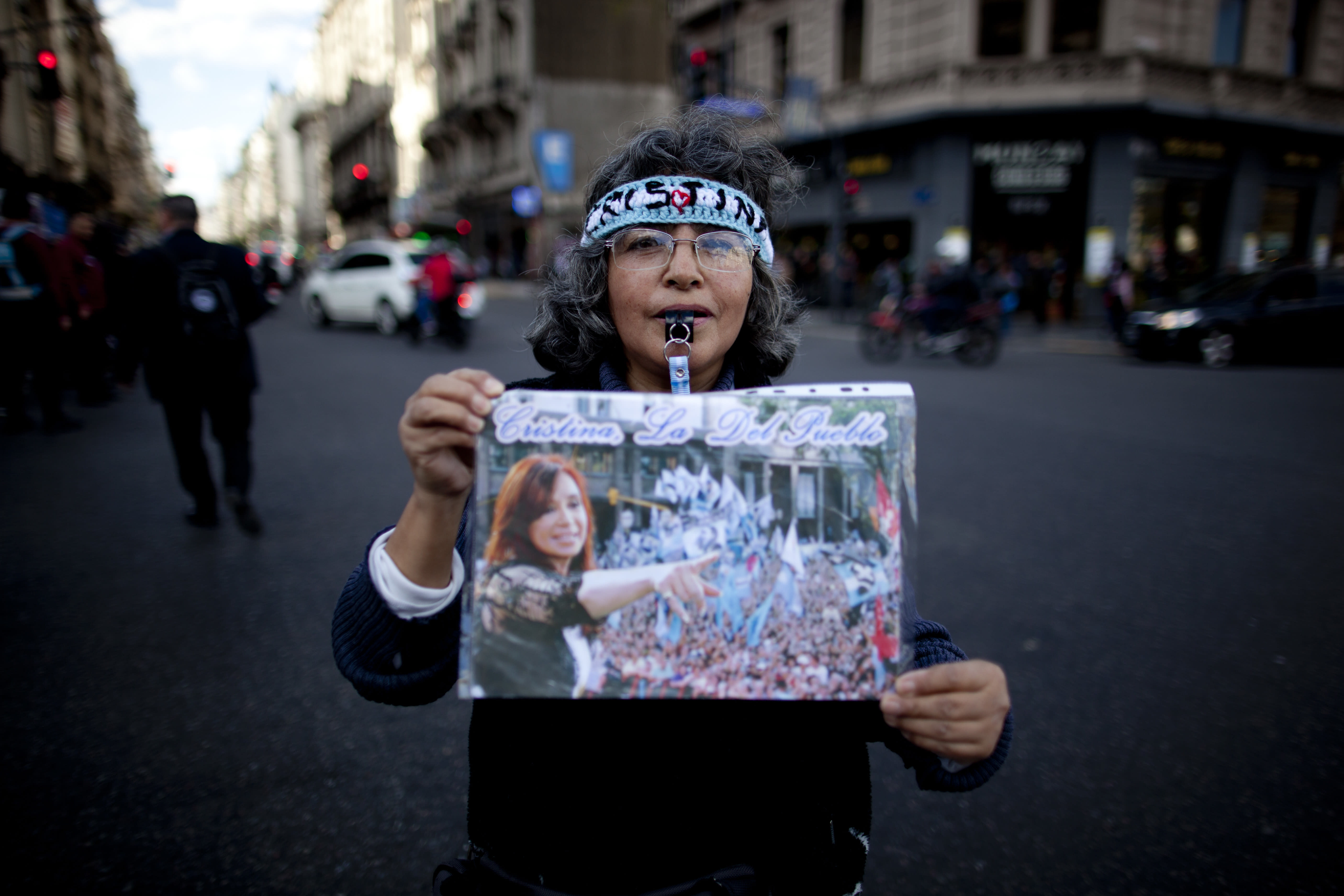 """In this Oct. 3, 2018 photo, Teresa Rollano, who is employed as a maid, holds up an a collage of former President Cristina Fernandez she keeps in a plastic protective sleeve, during a demonstration demanding improved conditions for disabled retirees, in Buenos Aires, Argentina. """"Many women voted in the government of Mauricio Macri and now they regret it,"""" said Rollano, during the demonstration where protesters chanted, """"Stay strong, Cristina"""" and held signs saying, """"Now more than ever, soldiers of Cristina."""" (AP Photo/Natacha Pisarenko)"""