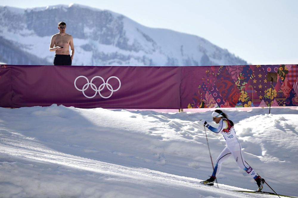 A shirtless spectator watches Sweden's Charlotte Kalla compete during the women's 10K classical-style cross-country race at the 2014 Winter Olympics, Thursday, Feb. 13, 2014, in Krasnaya Polyana, Russia. Kalla won the silver medal
