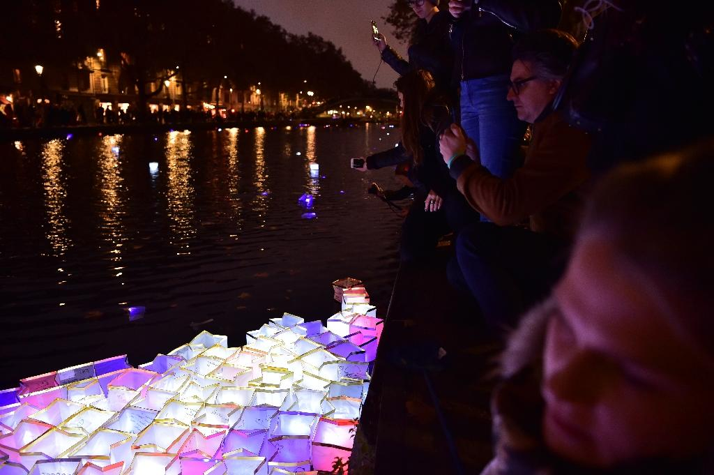 People set afloat lanterns at the Canal Saint-Martin in Paris on November 13, 2016 (AFP Photo/Christophe Archambault)
