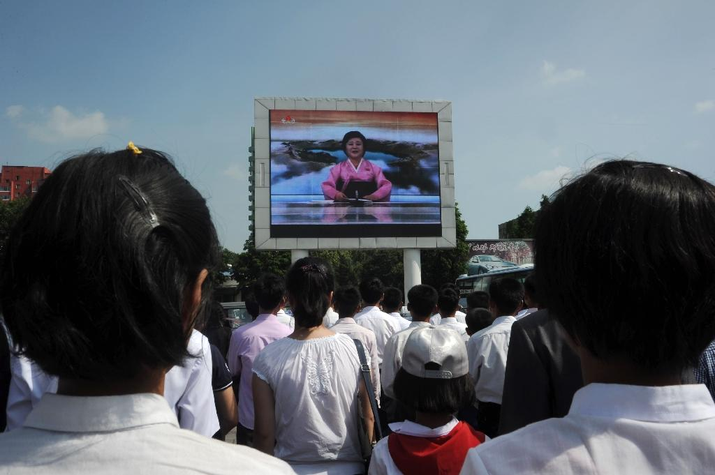 """Pyongyang residents watch TV announcer Ri Chun-Hee speak about the successful launch of the intercontinental ballistic missile """"Hwasong-14"""" on a big screen near the Pyongyang Railway Station in Pyongyang on July 4, 2017 (AFP Photo/Kim Won-Jin)"""