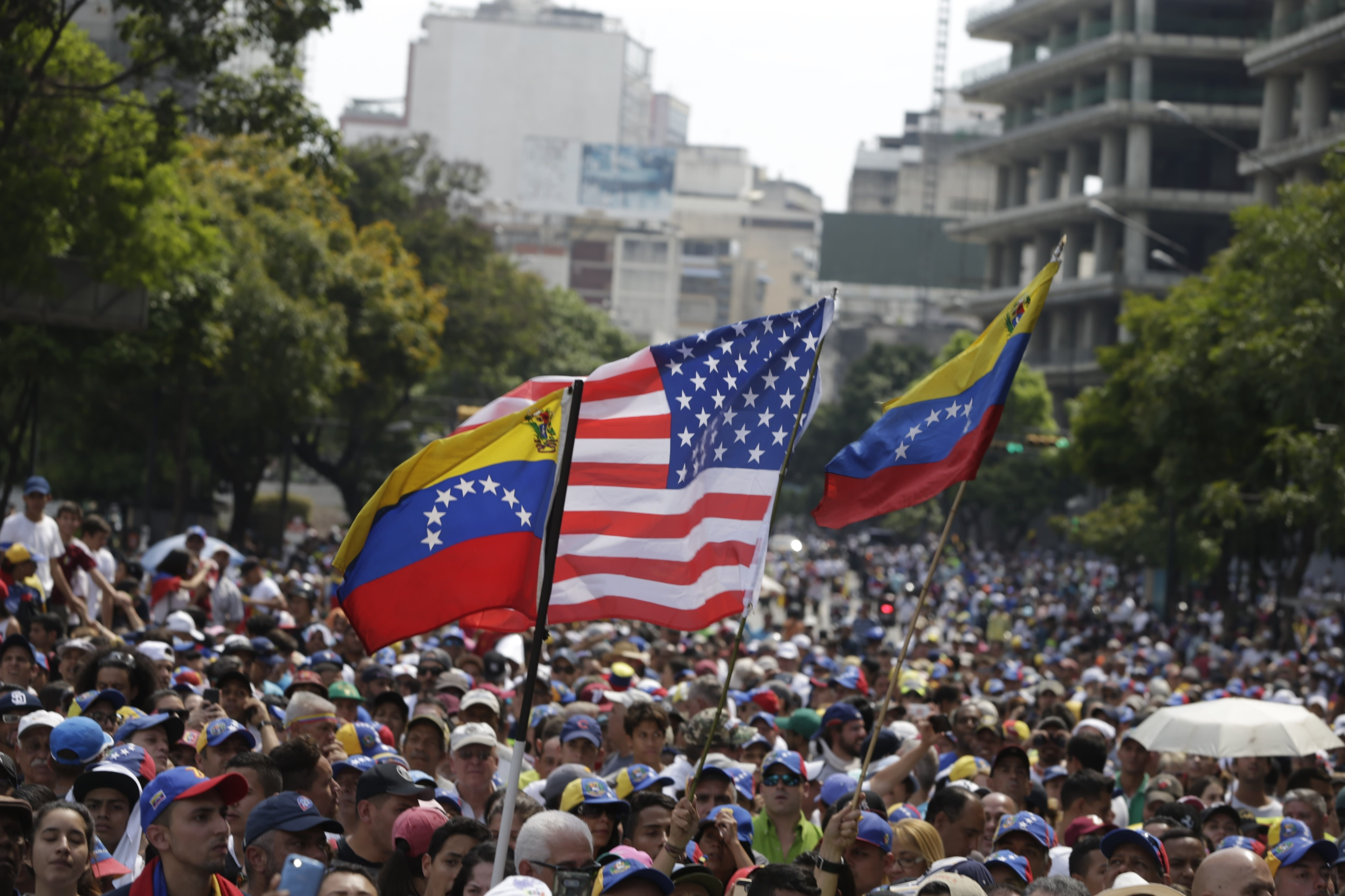Supporters holds Venezuelan and U.S. national flags as they listen to opposition leader Juan Guaidó speak during a rally in Caracas, Venezuela, Wednesday, May 1, 2019. Guaidó called for Venezuelans to fill streets around the country Wednesday to demand President Nicolas Maduro's ouster. Maduro is also calling for his supporters to rally. (AP Photo/Martin Mejia)