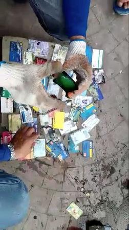 Sanitation workers sort out credit cards and IDs after retrieving wallets from a drain, after local media reported that a stash of wallets were clogging a canal in Poblacion, Batangas City, Philippines October 16, 2018, in this still image taken from a video obtained from social media. Domav Panganiban/via REUTERS