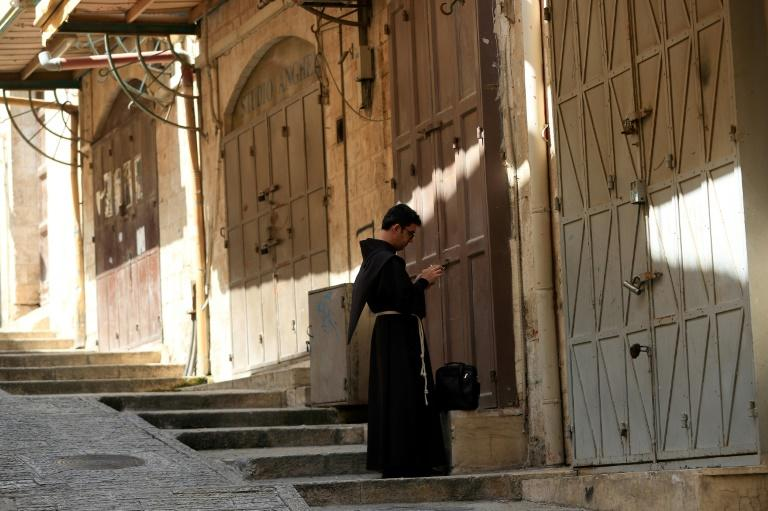 A Fransiscan friar stops in front of closed shops in the Old City of Jerusalem after Israel imposed tight restrictions to contain COVID-19 (AFP Photo/Emmanuel DUNAND)