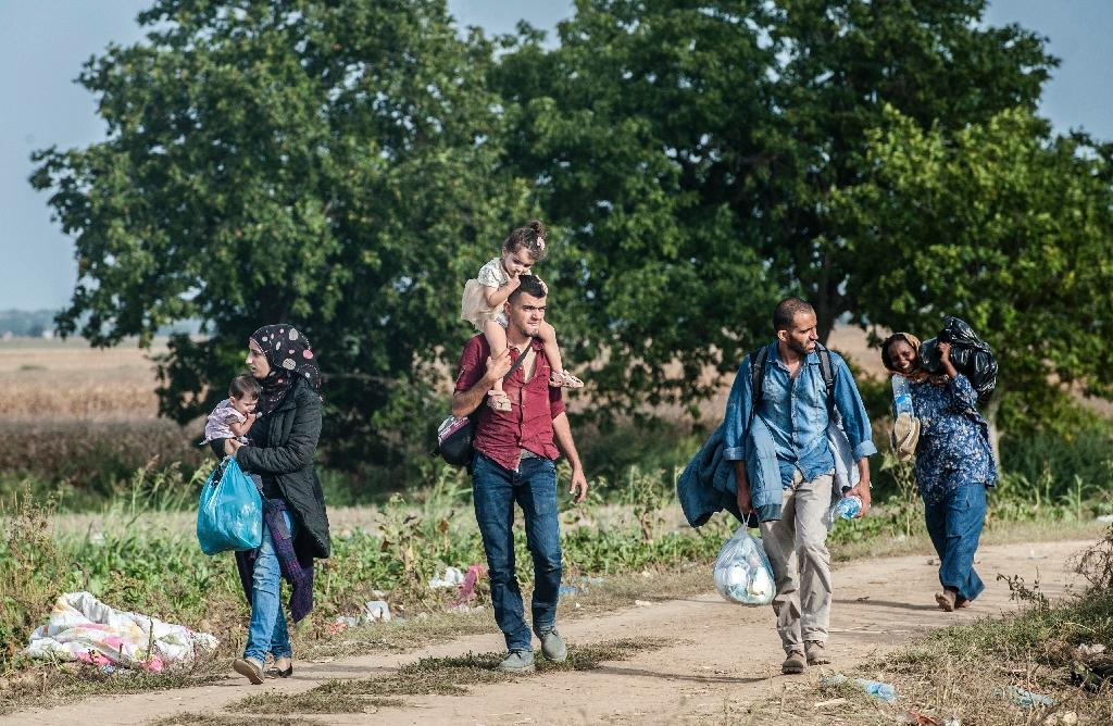 A group of migrants walk down a dirt road towards the Serbia-Croatia border, near the western-Serbia town of Sid, on September 19, 2015