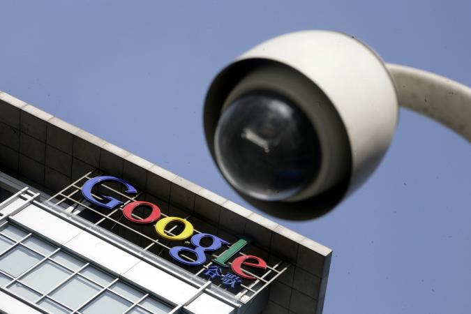 The Google logo is seen on the top of its China headquarters building behind a road surveillance camera in Beijing January 26, 2010. Chinese state media stepped up their war of words with the United States over Internet control on Tuesday, with a top newspaper claiming a U.S. conspiracy and saying China can live without Google. This logo has been updated and is no longer in use.   REUTERS/Jason Lee(CHINA - Tags: BUSINESS POLITICS SCI TECH)