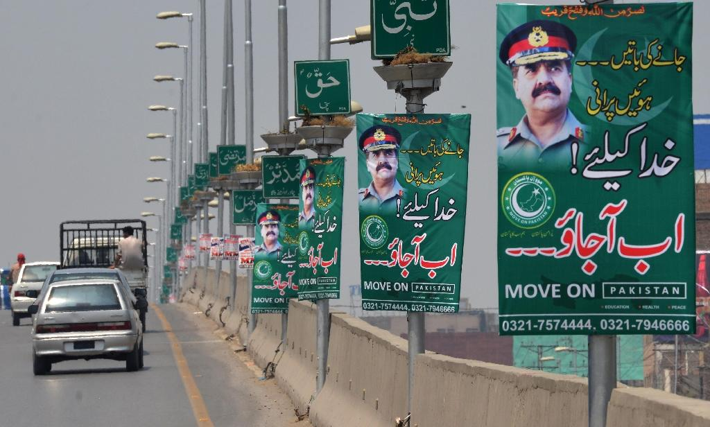 Pakistani commuters drive past posters in Peshawar begging the army to launch a coup (AFP Photo/A Majeed)