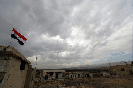 A Syrian flag is seen during an evacuation of rebels and civilians from Beit Jann, in Mogher al-Meer village, Syria December 29, 2017. REUTERS/Omar Sanadiki