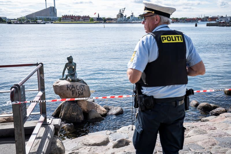 """Police officer stands in front of a graffiti reading """"Racist Fish"""" written on a statue of """"The Little Mermaid"""" in Copenhagen"""