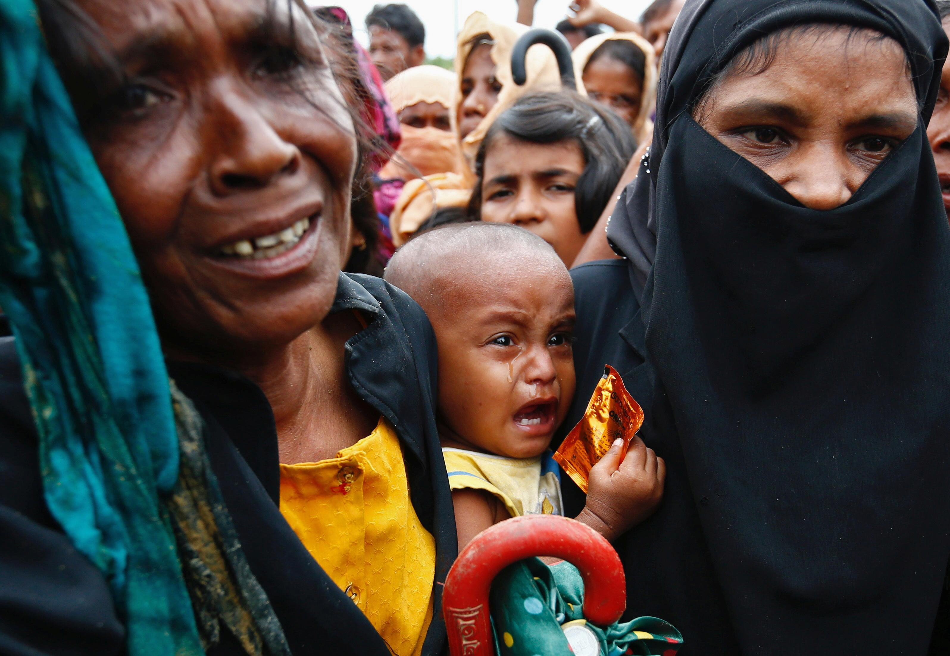 <p>A Rohingya refugee baby cries as his mother jostles for aid in Cox's Bazar, Bangladesh, Sept. 20, 2017. (Photo: Danish Siddiqui/Reuters) </p>