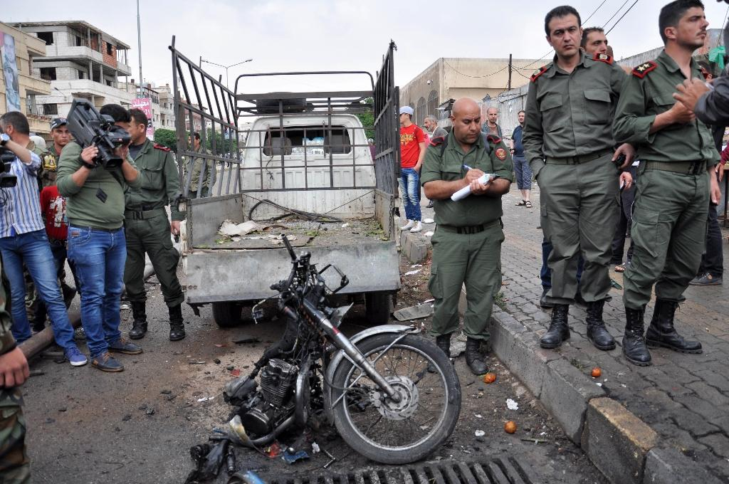 Syrian security personnel gather around the remains of a motorcycle after a double bomb blast in the Wadi Dahab neighbourhood of Homs, on May 12, 2015 (AFP Photo/)