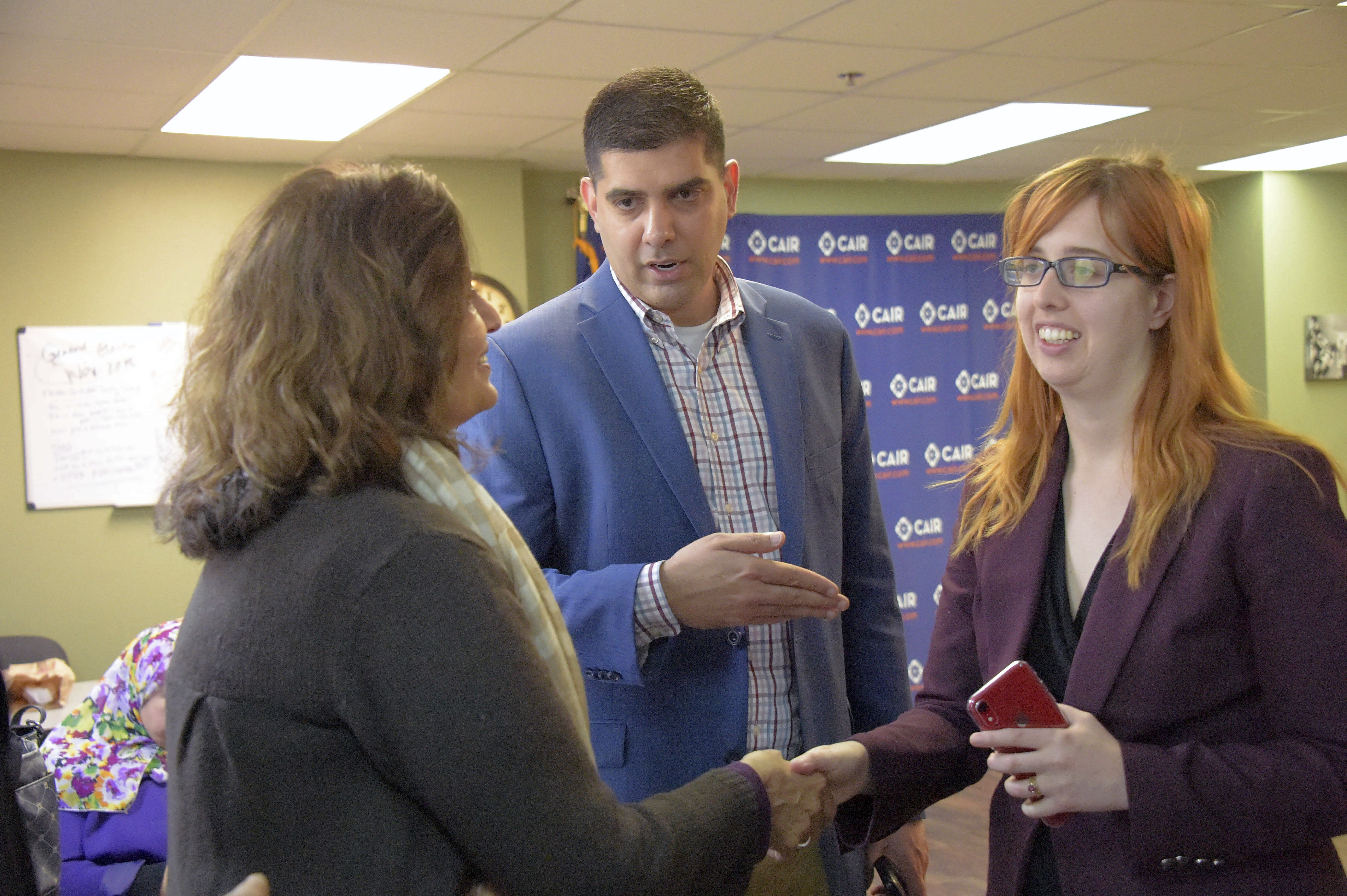 Saqib Ali introduces CAIR attorney Carolyn Homar, right, to his mother Samina Ali, following at a press conference, Wednesday, Jan. 9, 2019, in Catonsville, Md., announcing a legal challenge to Maryland's anti-BDS Executive Order. Maryland's ban on contracting with businesses that boycott Israel tramples on the First Amendment rights the software engineer who advocates for Palestinians, a Muslim civil rights group claims in a lawsuit filed Wednesday. (Karl Merton Ferron/The Baltimore Sun via AP)