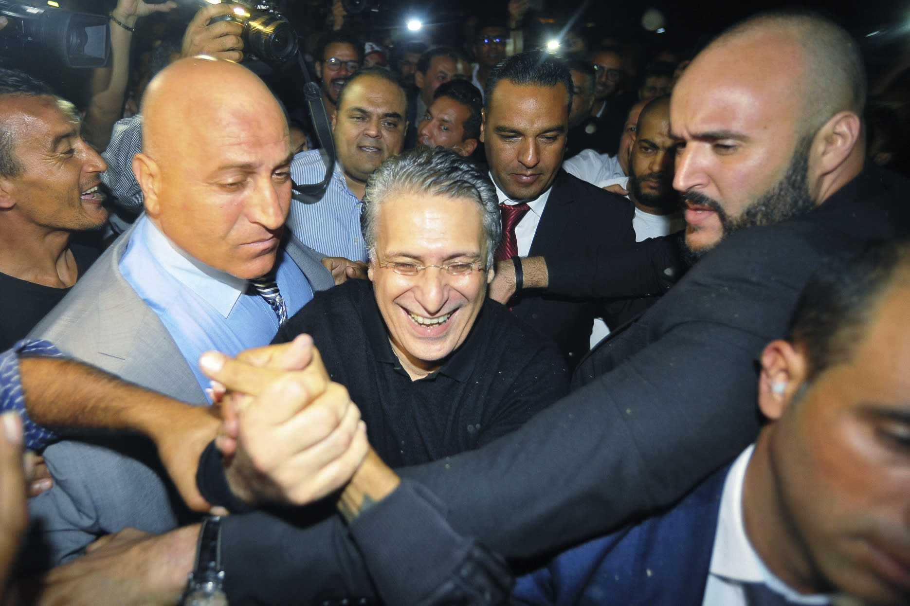 Tunisian presidential candidate and media mogul Nabil Karoui, center, is greeted by jubilant crowds after he was released from prison in Mannouba, Tunisia, Wednesday Oct. 9, 2019, just four days before the upcoming presidential runoff election. Karoui has been jailed since August under investigation for alleged money laundering and tax fraud that he asserts as a politically motivated smear campaign. (AP Photo)