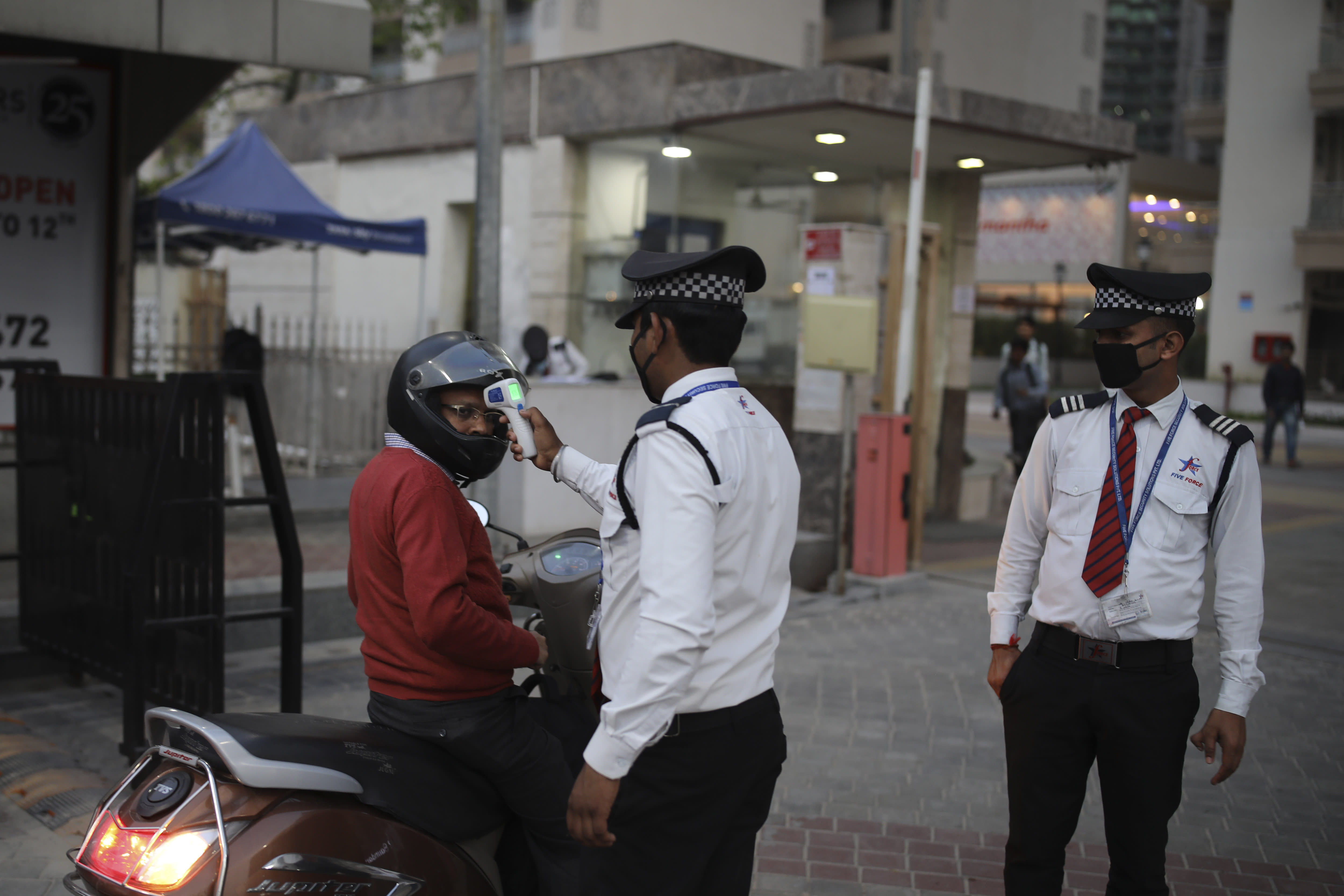 A private security guard checks the body temperature of a motorist as a precautionary measure against COVID-19 before letting him inside a residential complex in Greater Noida, a suburb of New Delhi, India, Saturday, March 21, 2020. For most people, the new coronavirus causes only mild or moderate symptoms. For some it can cause more severe illness. (AP Photo/Altaf Qadri)