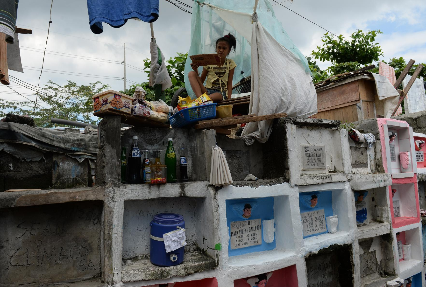 An temporary settler sells food to visitors from atop of the tombs at a cemetery in Manila, on October 31, 2014 (AFP Photo/Ted Aljibe)