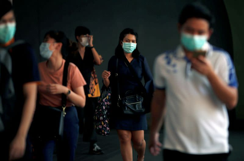 FILE PHOTO: People wear masks as a preventive measure against the coronavirus outbreak, in Bangkok