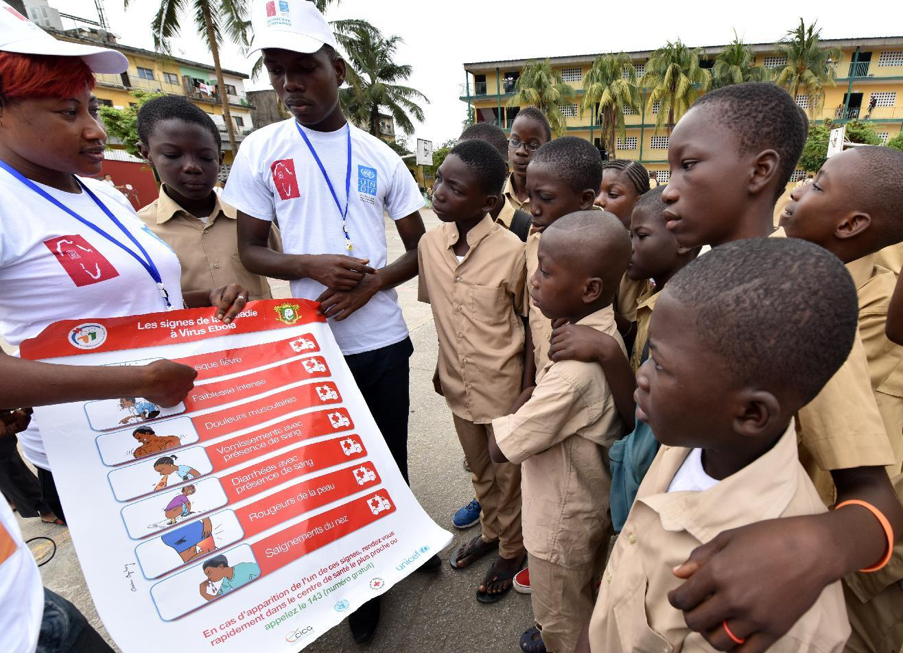 Volunteers wearing t-shirts of the United Nations Development Programme show a placard to raise awareness about the symptoms of the Ebola virus to students in Abidjan, on September 15, 2014 (AFP Photo/Sia Kambou)