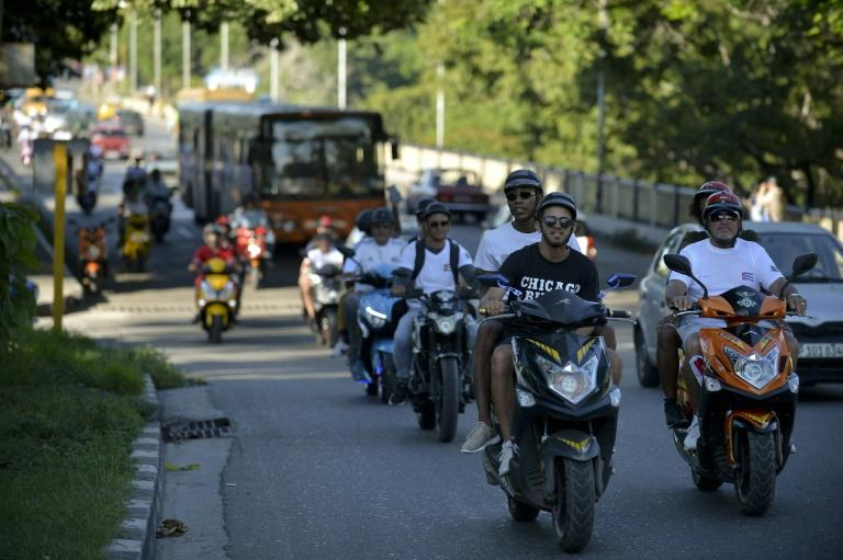 Electric motorcycle riders have come to the rescue of Cuban passengers delayed by fuel shortages (AFP Photo/YAMIL LAGE)