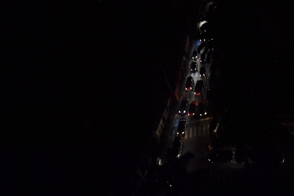 Drivers try to move along a pitch-dark, congested street during a new power outage in Caracas on March 29, 2019 (AFP Photo/YURI CORTEZ)
