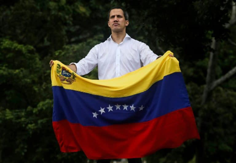 Venezuelan opposition leader Juan Guaido unfurls the country's flag during a rally in Caracas (AFP Photo/Cristian HERNANDEZ)