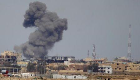 A plume of smoke rises above a building during an air strike in Tikrit