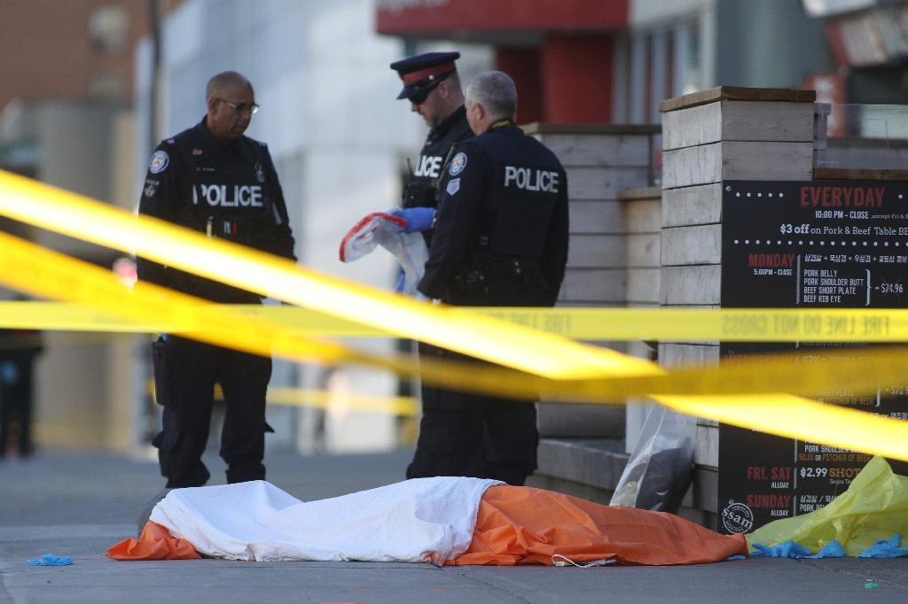 Police officers stand near one of the bodies on the street after a truck drove up on the curb and hit several pedestrians in Toronto (AFP Photo/Lars Hagberg)