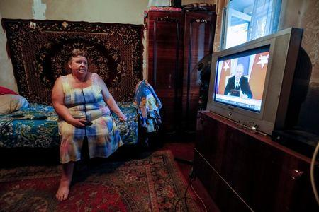 Ukrainian pensioner Olha Shazhkova shows one of the Russian channels available on her television at home in the front line town of Avdeyevka, Ukraine, August 10, 2016. REUTERS/Gleb Garanich