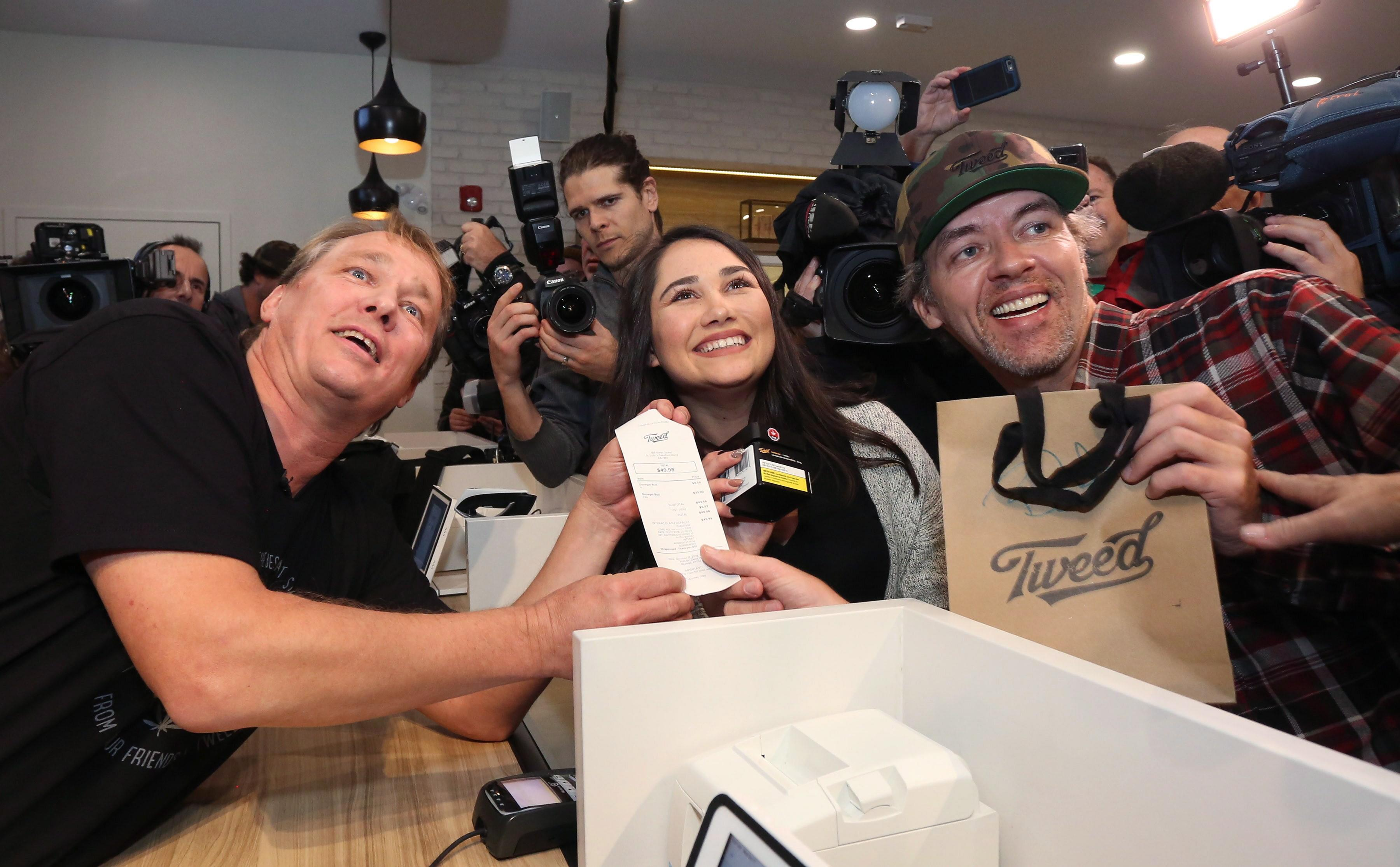 <p>Canopy Growth Corporation CEO Bruce Linton, left to right, poses with the receipt for the first legal cannabis for recreation use sold in Canada to Nikki Rose and Ian Power at the Tweed shop on Water Street in St. John's N.L. at 12:01 am NDT on Wednesday October 17, 2018.<br>(Photo from Paul Daly, The Canadian Press) </p>