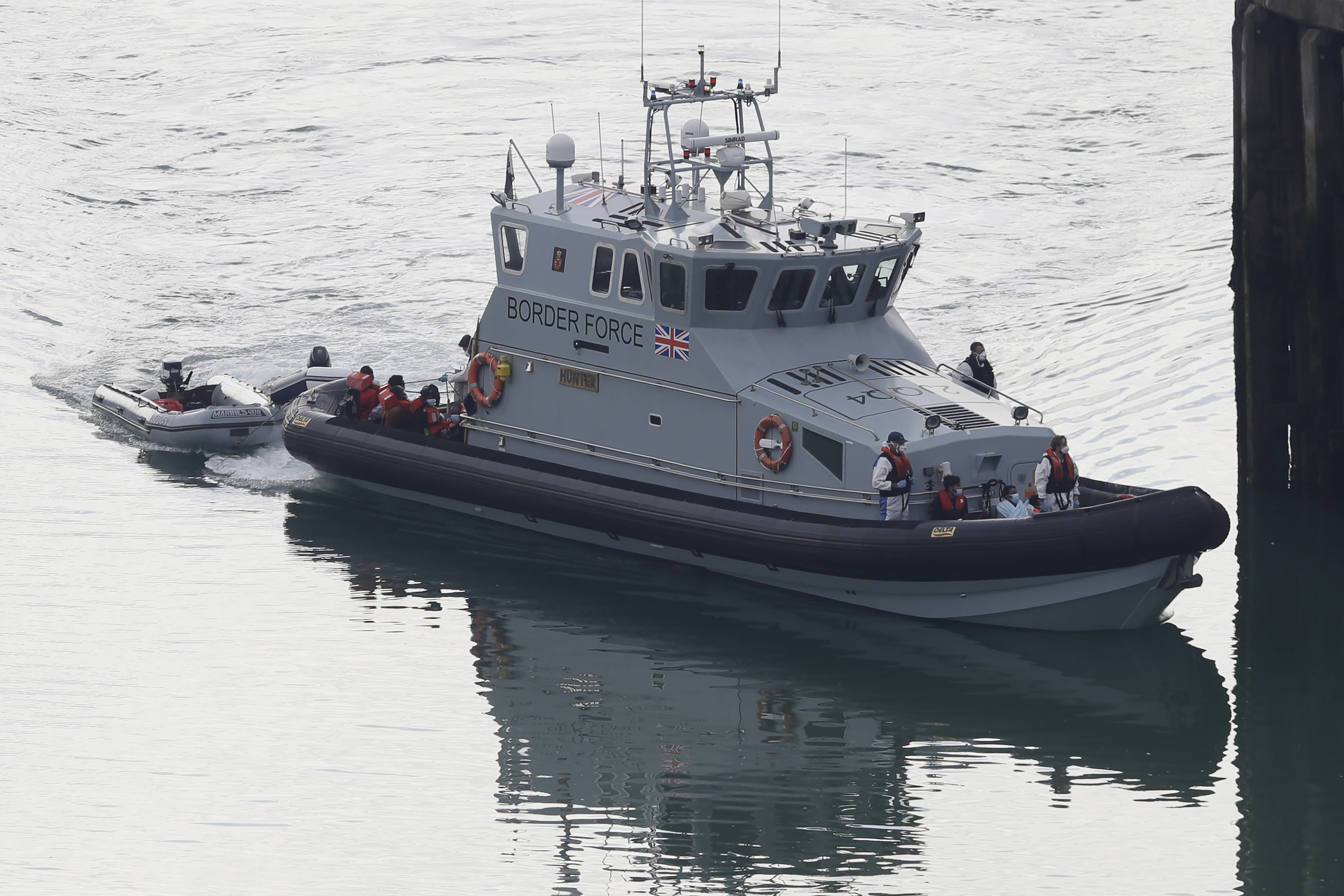 A Border Force vessel brings a group of people thought to be migrants into the port city of Dover, England, from small boats, Saturday Aug. 8, 2020. The British government says it will strengthen border measures as calm summer weather has prompted a record number of people to attempt the risky sea crossing in small vessels, from northern France to England. (AP Photo/Kirsty Wigglesworth)