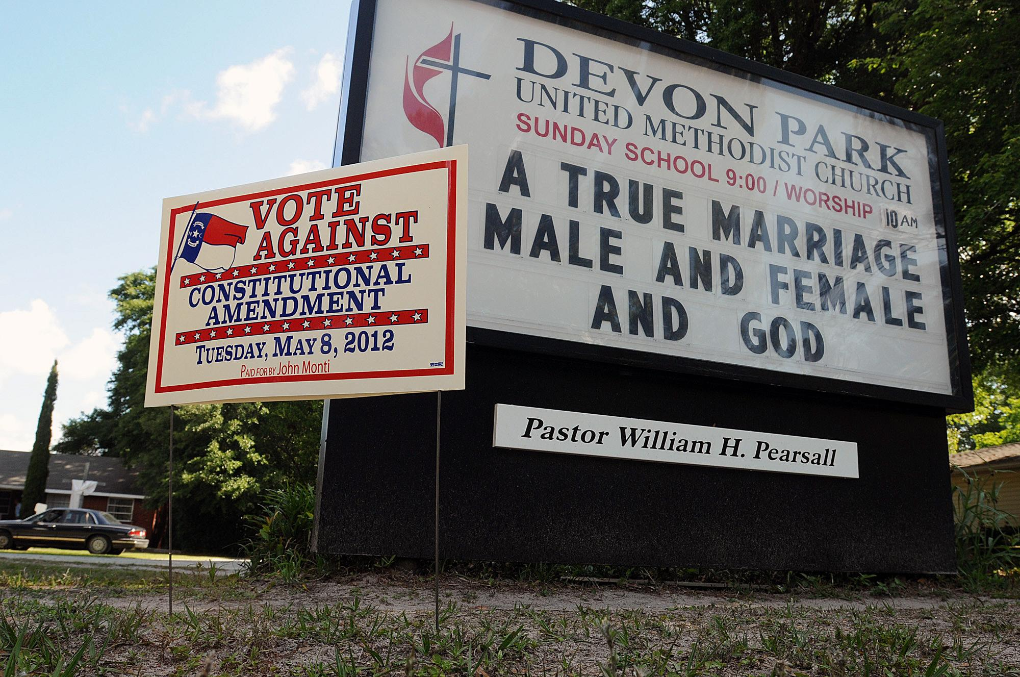 Signs display messages about gay marriage in front of the Devon Park United Methodist Church polling site on Tuesday, May 8, 2012, in Wilmington, N.C. North Carolina could be the next state to pass a constitutional amendment defining marriage as solely between a man and a woman. Voters are casting their ballots Tuesday. (AP Photo/The Star-News, Ken Blevins)