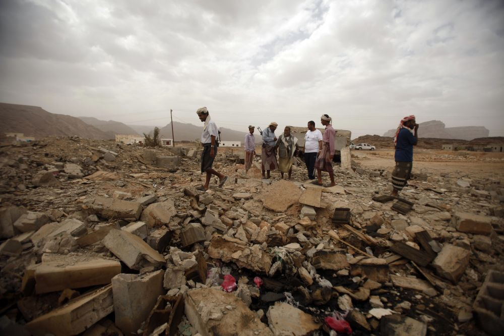 Tribesmen stand on the rubble of a building destroyed by a U.S. drone air strike