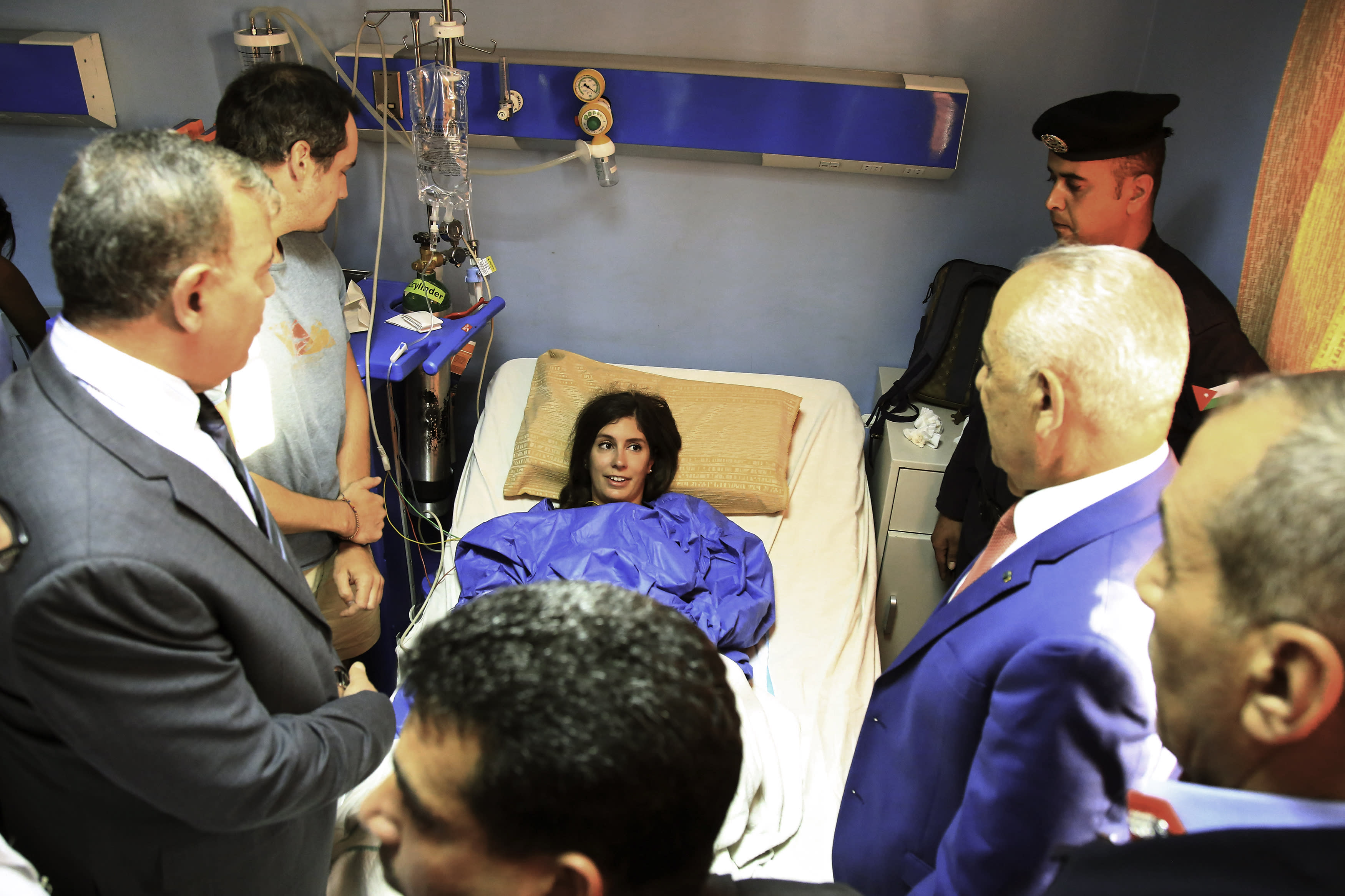 CORRECTS LOCATION OF HOSPITAL TO JERAASH -Royal Court chief Yousef Issawi, right, visits one of the victims of a knife attack in Jerash, Jordan on Wednesday, Nov. 6, 2019. A young man from a Palestinian refugee camp on Wednesday stabbed eight people, including four foreign tourists and their tour guide, at a popular archaeological site in Jeraash, in northern Jordan, security officials said. The wounded included three Mexican tourists and a Swiss woman, according to Jordan's Public Security office. Along with the tour guide, three other Jordanians, including two security officers and a bus driver, were also hurt before the attacker was subdued and arrested. (AP Photo/Raad Adayleh)